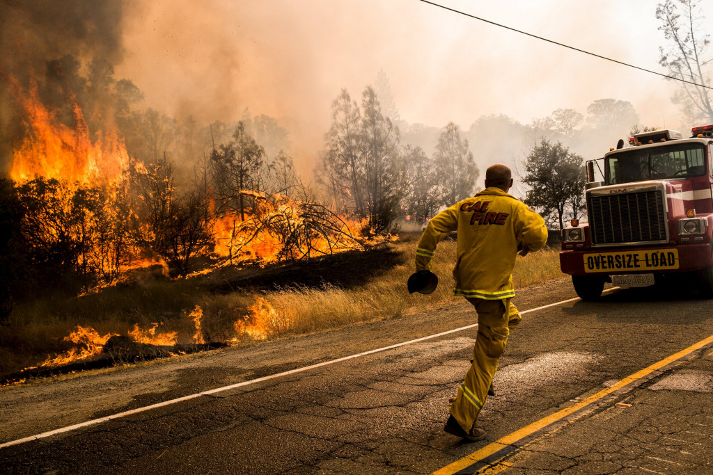 A Cal Fire firefighter races to move a truck before it's overrun at the Rocky Fire in Lake County, California July 30, 2015. The Rocky Fire broke out on Wednesday afternoon in Lake County, 110 miles (180 km) north of San Francisco. By Thursday morning it had spread to 8,000 acres (3,237 hectares), according to the California Department of Forestry and Fire Protection, known as Cal Fire.  REUTERS/Max Whittaker