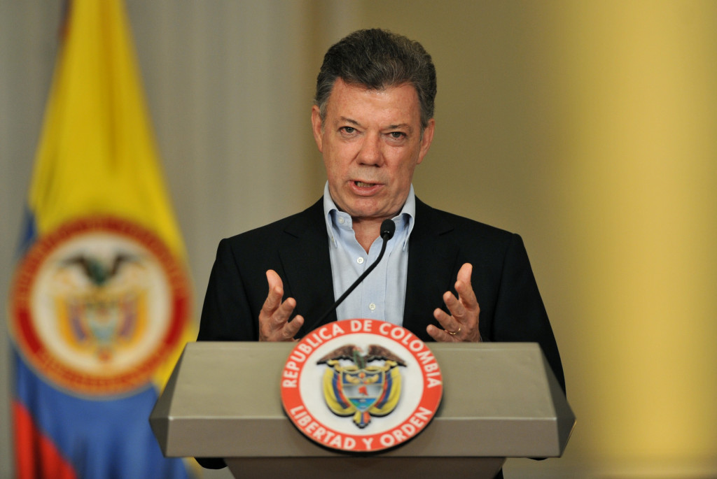 Colombian President Juan Manuel Santos gestures during a joint press conference with former US president and 2002 Nobel peace prize laureate, Jimmy Carter (out of frame) after a meeting on January 12, 2013, at Narino Presidential Palace in Bogota, Colombia. Carter is on a two day visit to Bogota to assess the ongoing peace talks between Colombia's government and its largest leftist guerrilla group, the Revolutionary Armed Forces of Colombia (FARC). This meeting will take place before the government delegation's trip to Havana on Monday to resume talks with FARC's delegation and start the third round of peace negotiations. AFP PHOTO/Guillermo LEGARIA        (Photo credit should read GUILLERMO LEGARIA/AFP/Getty Images)